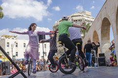 Birra-Sheva, ISRAELE - 5 marzo 2015: I ragazzi e le ragazze hanno eseguito sulle biciclette con una ruota sulla scena della via - Fotografia Stock