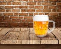 Birra sulla tavola di legno con il fondo del mattone Fotografie Stock Libere da Diritti