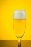 Birra in un vetro sul fondo giallo della lampadina Immagine Stock