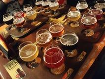 Birre assortite in un volo pronto per avere un sapore immagini stock