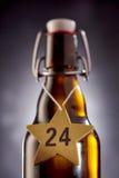 24 birre di natale sulla stella intorno alla bottiglia Immagini Stock Libere da Diritti