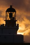 Birsay lighthouse. Orkney, in silhouette at sunset stock image