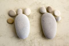 Two tiny stone feet and ten toes on beige background, stone in the shape of a human feet. Birth announcement card, two tiny stone feet and ten toes on beige Stock Photos