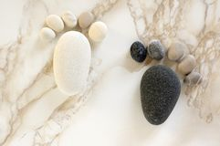 Two tiny stone feet and ten toes on beige background, stone in the shape of a human feet. Birth announcement card, two tiny stone feet and ten toes on beige Stock Images