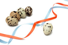 The birth awaiting. Five quail eggs and two color ribbons Royalty Free Stock Images