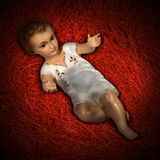 Birth of Baby Jesus on the Red Straw. Baby Jesus figurine lying in manger on red straw background with shadows Stock Image