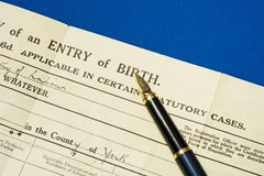 Birth certificate. A macro image of a hand written birth certificate with gold nibbed fountain pen placed upon it Stock Image