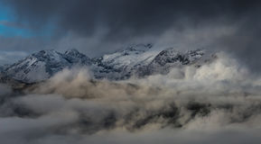 Birth of clouds high in mountains on a foggy morning. Stock Photos