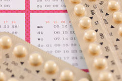 Birth control pills on a calender Stock Photos