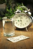 Birth control pills time. Birth control pills and a glass of water on a bedside table royalty free stock image
