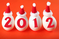 Birth of the new 2012 year. Eggs in Santa's hats with 2012 inscription, isolated on red royalty free stock images
