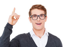 The birth of new idea. Cheerful young man pointing up and smiling at camera while standing isolated on white Stock Photography