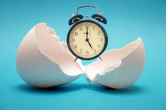 Birth of new time. From the broken egg there is an alarm clock stock photos