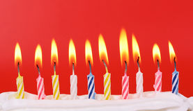Birthday. 10 lit birthday candles in bright colors with red background Stock Photos