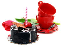 Birthday. Chocolate cake with a candle and red cup on a white background Royalty Free Stock Images