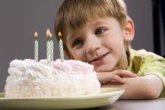 Birthday. Happy blond boy with birthday cake looking at the candles Royalty Free Stock Photo