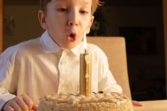 Birthday. Kid posing when blowing birthday candle Stock Photos