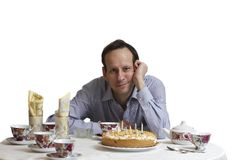 Birthday. The man in a blue shirt sits near to an anniversary pie on which burn candles Royalty Free Stock Images