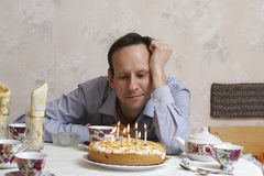 Birthday. The man in a blue shirt sits near to an anniversary pie on which burn candles Stock Images