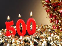 Birthday-anniversary candle showing Nr. 500. Lit red candle good for an anniversary or birthday background royalty free stock photo