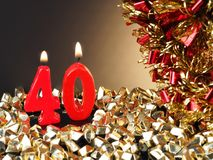 Birthday-anniversary candle showing Nr. 40. Lit red candle good for an anniversary or birthday background Royalty Free Stock Photos