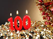 Birthday-anniversary candle showing Nr. 100. Lit red candle good for an anniversary or birthday background Stock Images