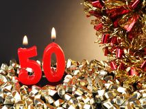 Birthday-anniversary candle showing Nr. 50. Lit red candle good for an anniversary or birthday background Royalty Free Stock Image