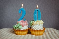 Birthday anniversary 20 years with cake and blue candles. Birthday anniversary 20 years with cupcakes and blue numbers candles on gray background Royalty Free Stock Photo