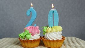 Birthday anniversary 20 years with cake and blue numbers candles. On gray background. Anniversary concept stock video