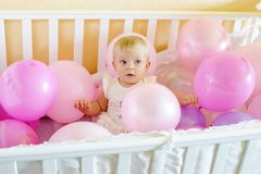 Birthday baby girl in the bed. With a lot of balloons royalty free stock photography