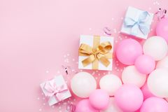 Birthday background with gift or present box, balloons and confetti on pink pastel table top view. Flat lay style. Birthday background with gift or present box Stock Image