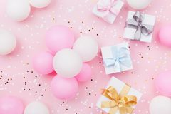 Birthday background with gift or present box, balloons and confetti on pink pastel table top view. Flat lay composition. Birthday background with gift or Royalty Free Stock Photo