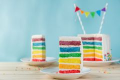Birthday background - striped rainbow cake with white frosting Royalty Free Stock Image