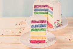 Birthday background - striped rainbow cake with white frosting Royalty Free Stock Images