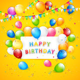 Birthday balloons and tinsel on yellow background Stock Image