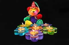 Birthday Bash. Happy Birthday teddy bear sits in front of flower shaped candles. Candles are burning and in fun colors of blue, purple, green and orange royalty free stock photo