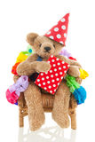 Birthday bear. Funny stuffed bear in birthday chair isolated over white background Royalty Free Stock Image