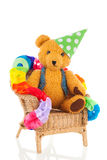 Birthday bear. Funny stuffed bear in birthday chair isolated over white background Stock Photos