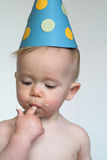 Birthday Boy. Image of an adorable 1 year old, wearing a paper hat, eating birthday cake Stock Image