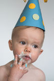 Birthday Boy. Image of an adorable 1 year old, wearing a paper hat, eating birthday cake royalty free stock photography
