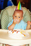 Birthday boy. 1 year old eating birthday cake Stock Image
