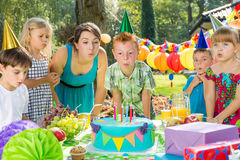 Birthday boy blowing up candles. Children and birthday boy blowing up candles on cake Stock Photos