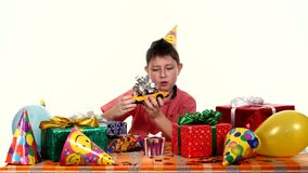 Birthday boy sitting at a small table with gifts stock video