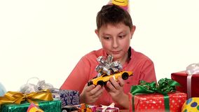 Birthday boy sitting at a small table with gifts stock video footage