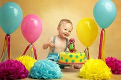 Birthday boy. Smiling boy sitting by the birthday cake Royalty Free Stock Image