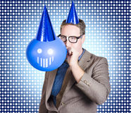 Birthday businessman blowing up smiling balloon Stock Images