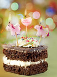 Birthday cake. Happy birthday cake with candle and pony against colorful bokeh background stock image