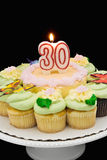 Birthday Cake. Surrounded by cupcakes with a burning 30 candle Stock Image