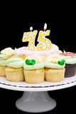 Birthday cake. With burning 75 candle. Pastel colored mini-cake surrounded by yellow and chocolate cupcakes. Isolated black background Stock Image