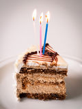 Birthday cake. A piece of birthday cake with three burning candles Royalty Free Stock Photos